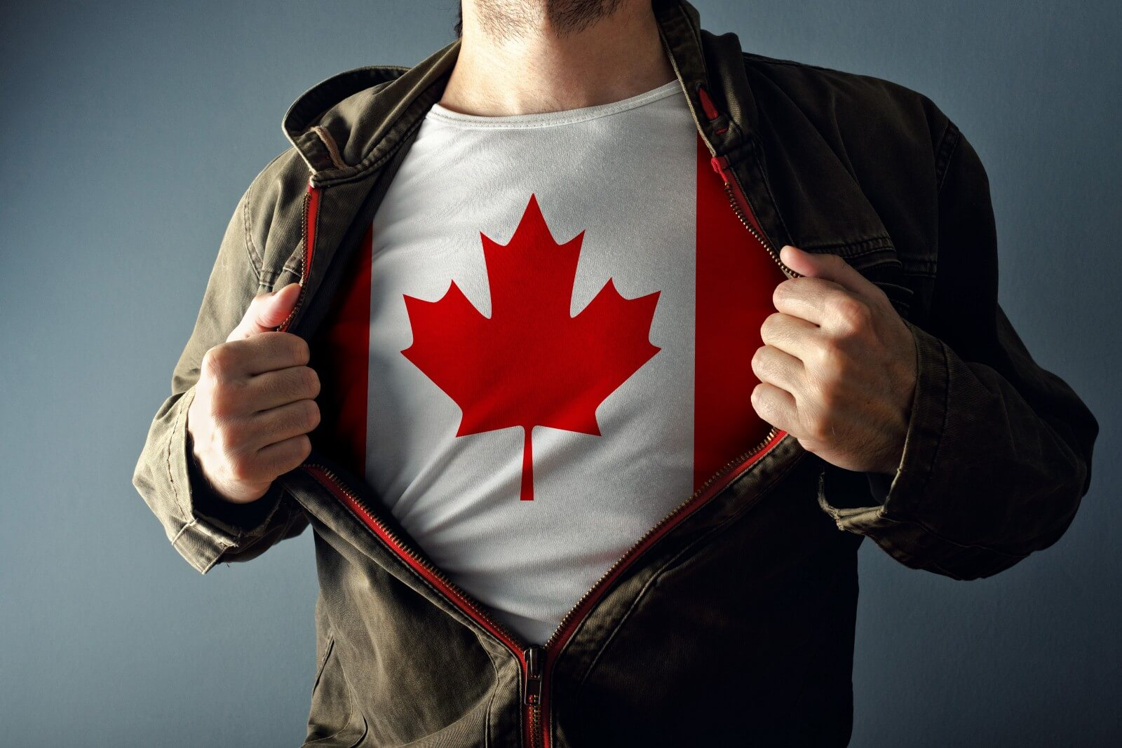 Man wearing dark leather zippered jacket partially opened to reveal a Canadian flag t-shirt
