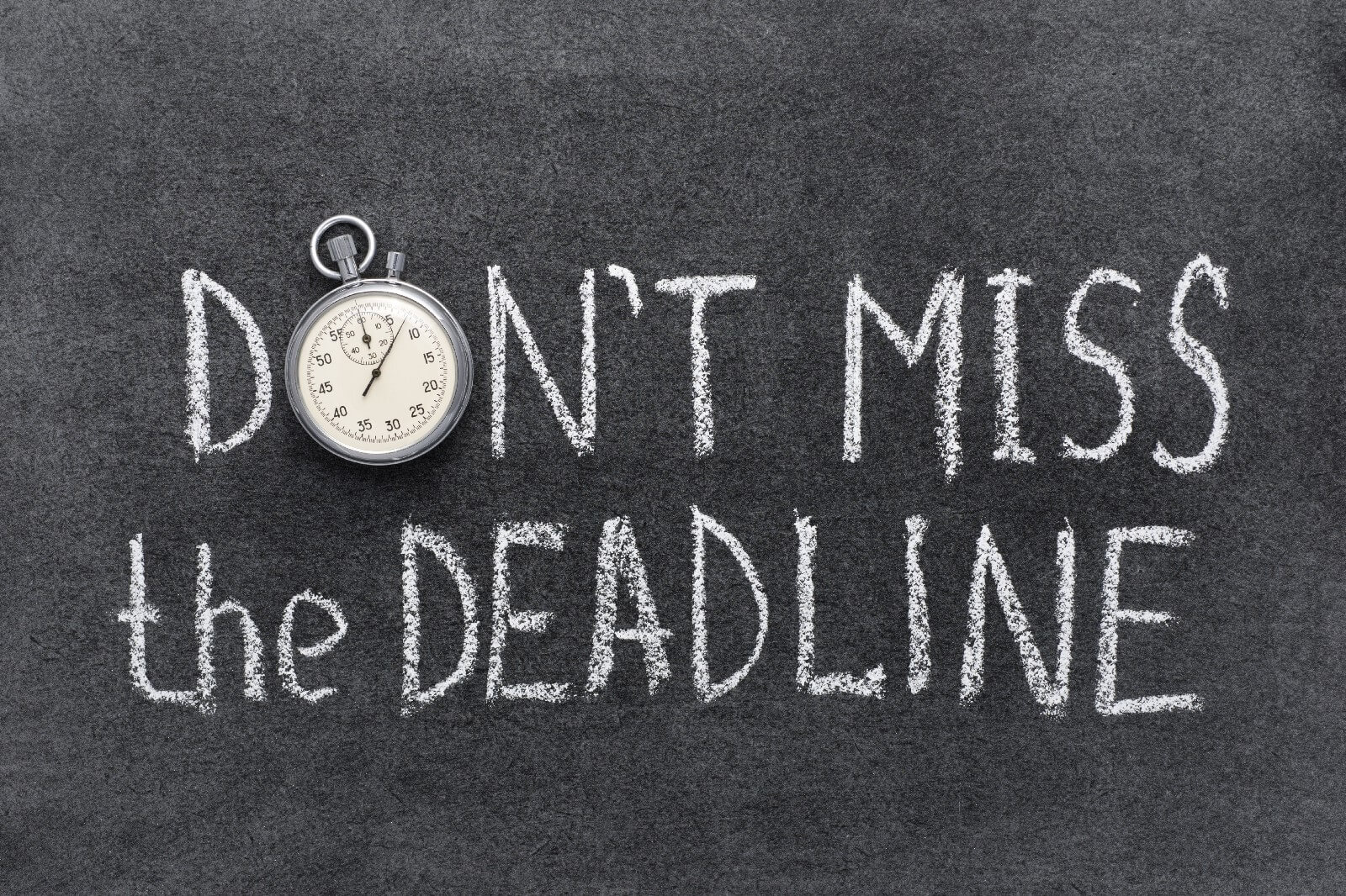 """Don't miss the Deadline"" written on a chalkboard in white chalk with a silver stopwatch in place of the letter ""o"" in ""don't"""
