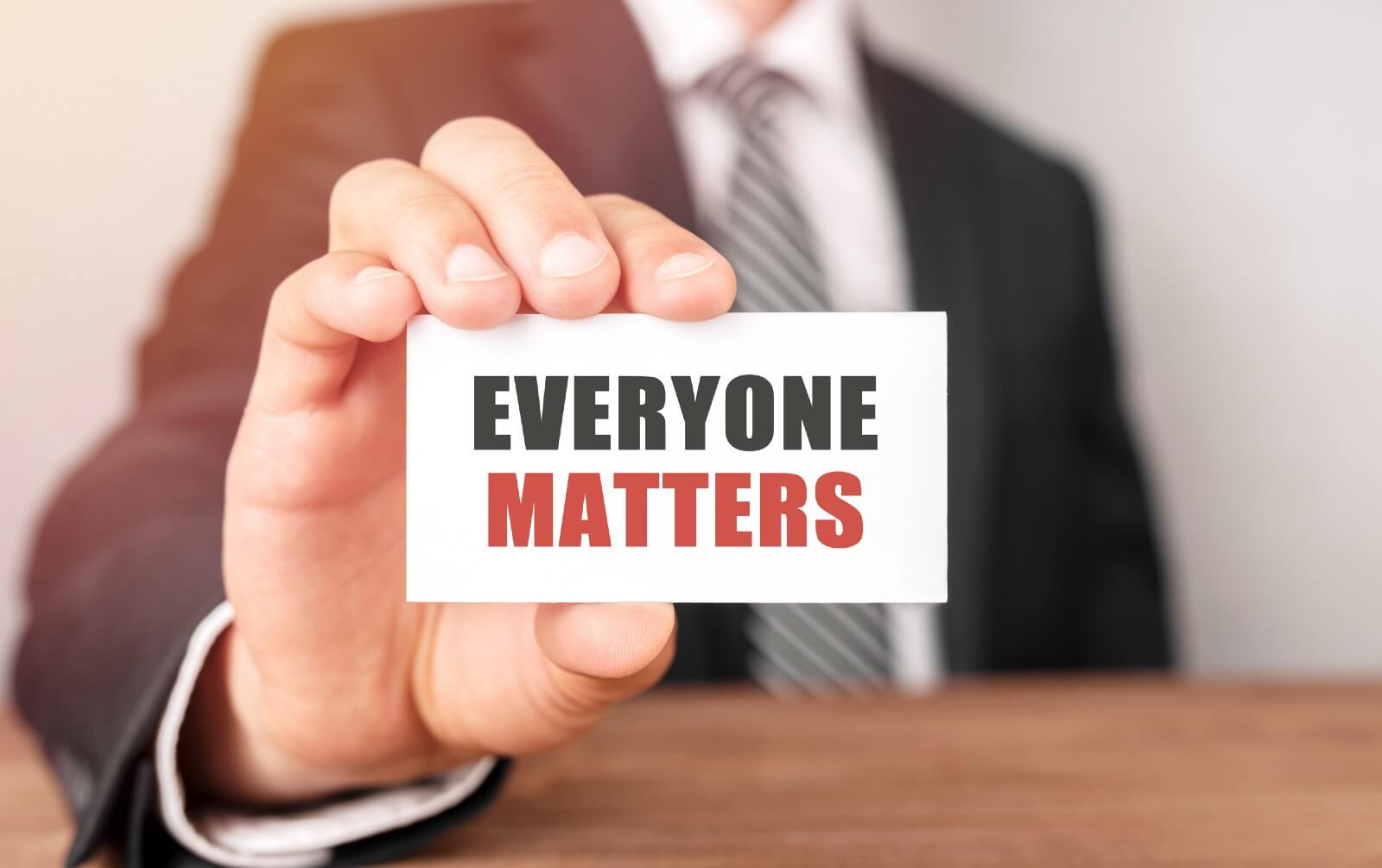 "Blurred man in a business suit holding a card that says ""everyone matters"""