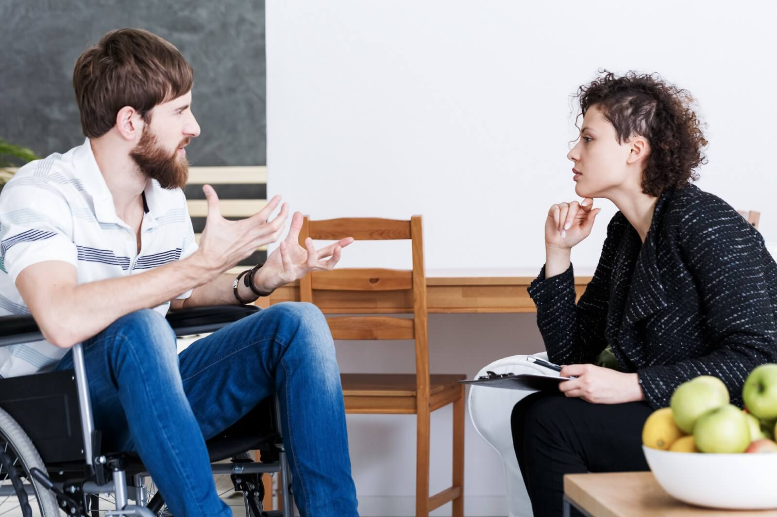 Man using wheelchair and woman engaging in conversation in a business setting