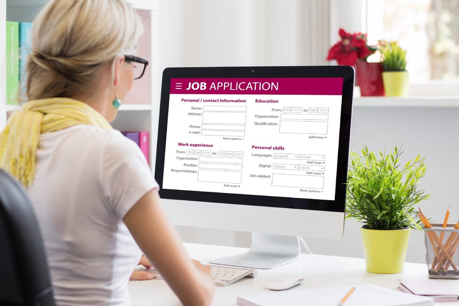 Woman sitting at business desk filling out digital job application