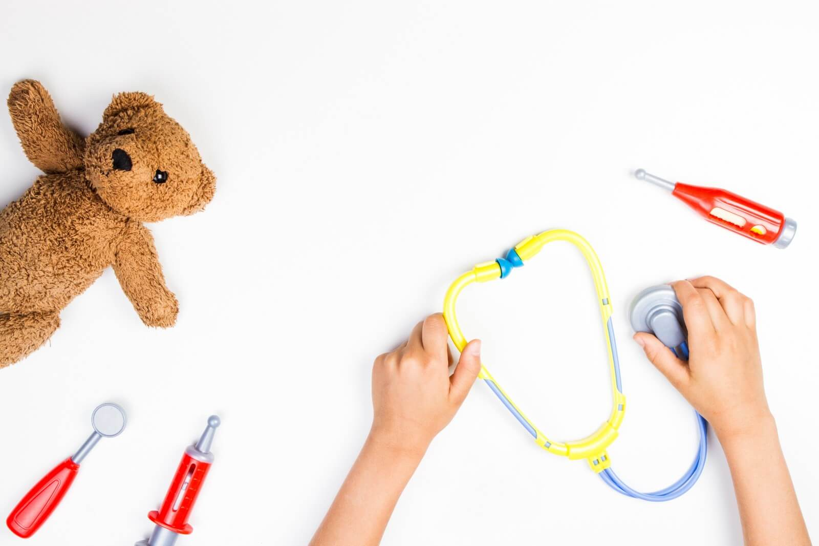 Child's hands holding toy stethoscope surrounded by toy medical equipment and a stuffed bear
