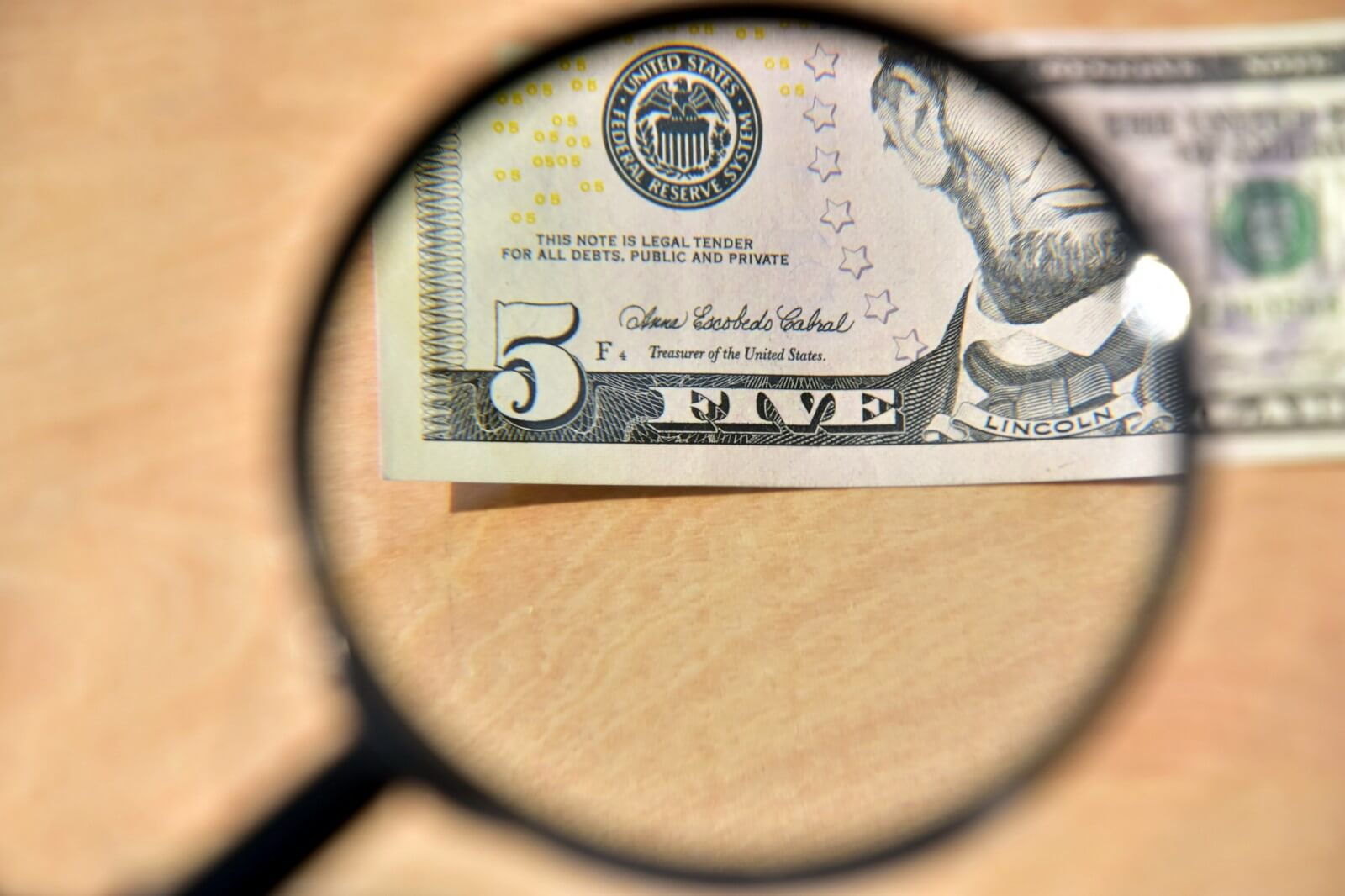 Five dollar bill on wooden table partially viewed through a magnifying glass