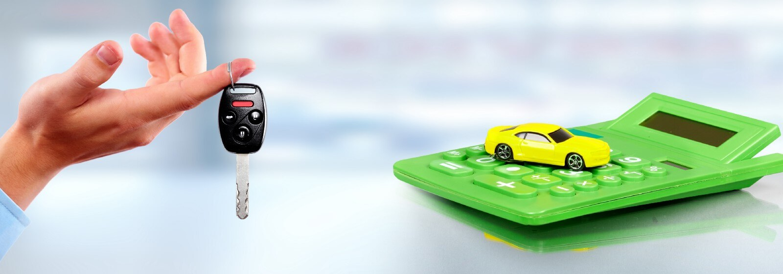 Hand with car key hanging from index finger, green calculator with yellow toy car on it