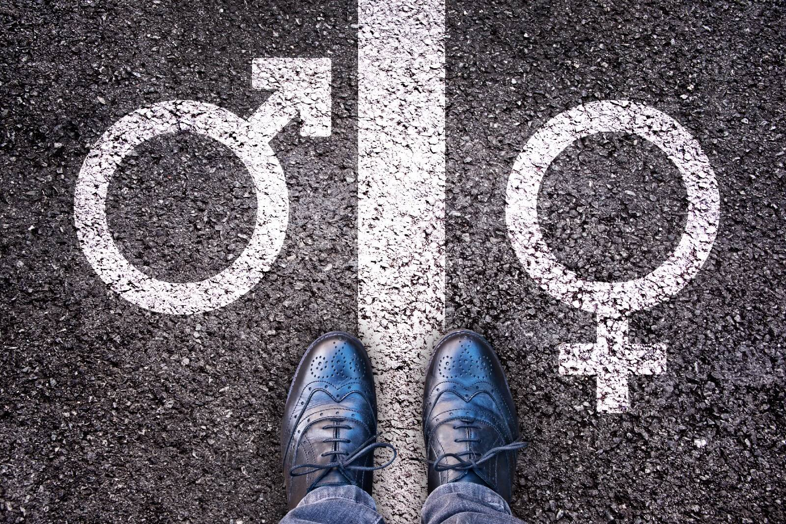 Shoes on asphalt straddling a line — symbol for male is on the left, symbol for female is on the right