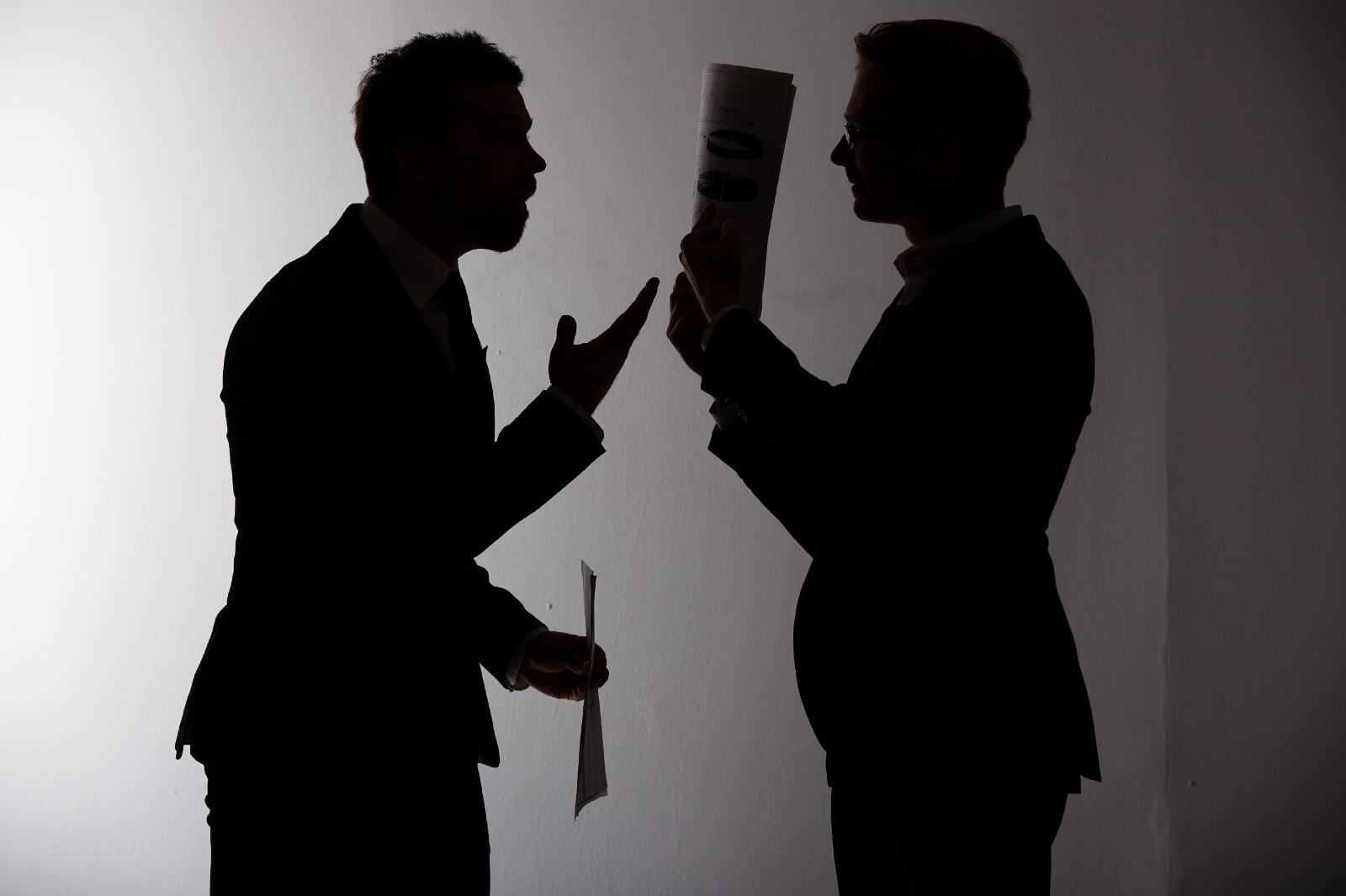 Two men in shadow, one arguing, the other hiding behind a file folder