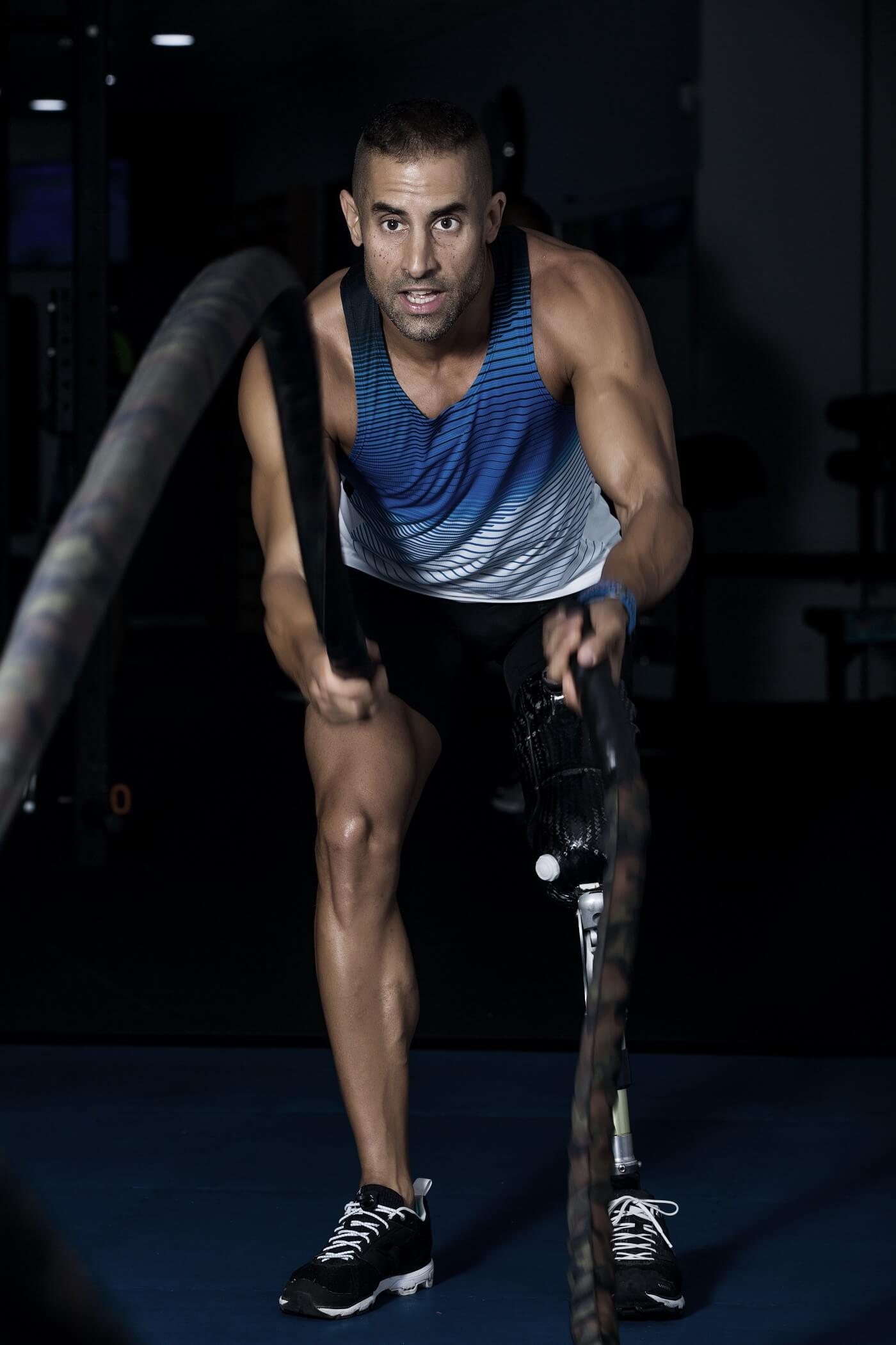 Man with prosthetic leg exercising in Gym