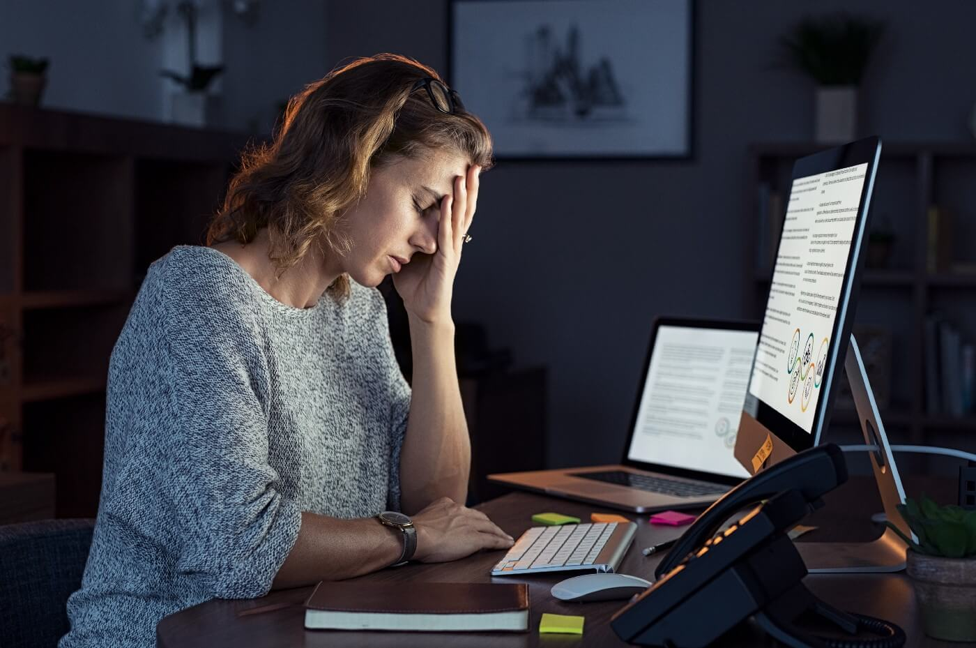 A woman at the desk, working on the computer and looking tired.