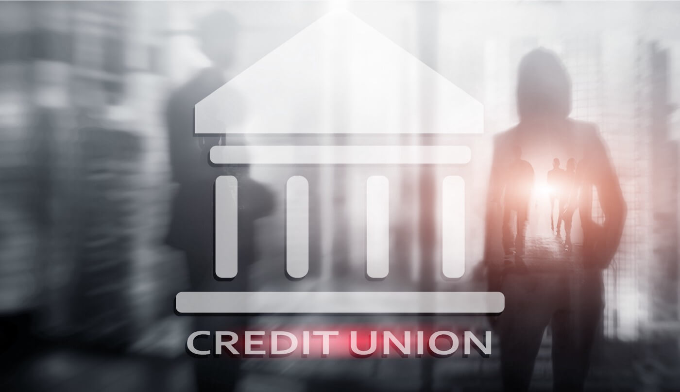 "Blurred background in black and white with people in an IT center, foreground is an icon of a building with the words ""Credit Union"" in white underneath"