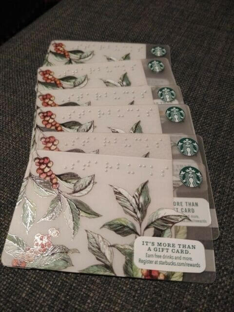 "Starbucks 2016 gift cards with the word ""Starbucks"" spelled out in Braille across the top. Folliage with red berries & logo"