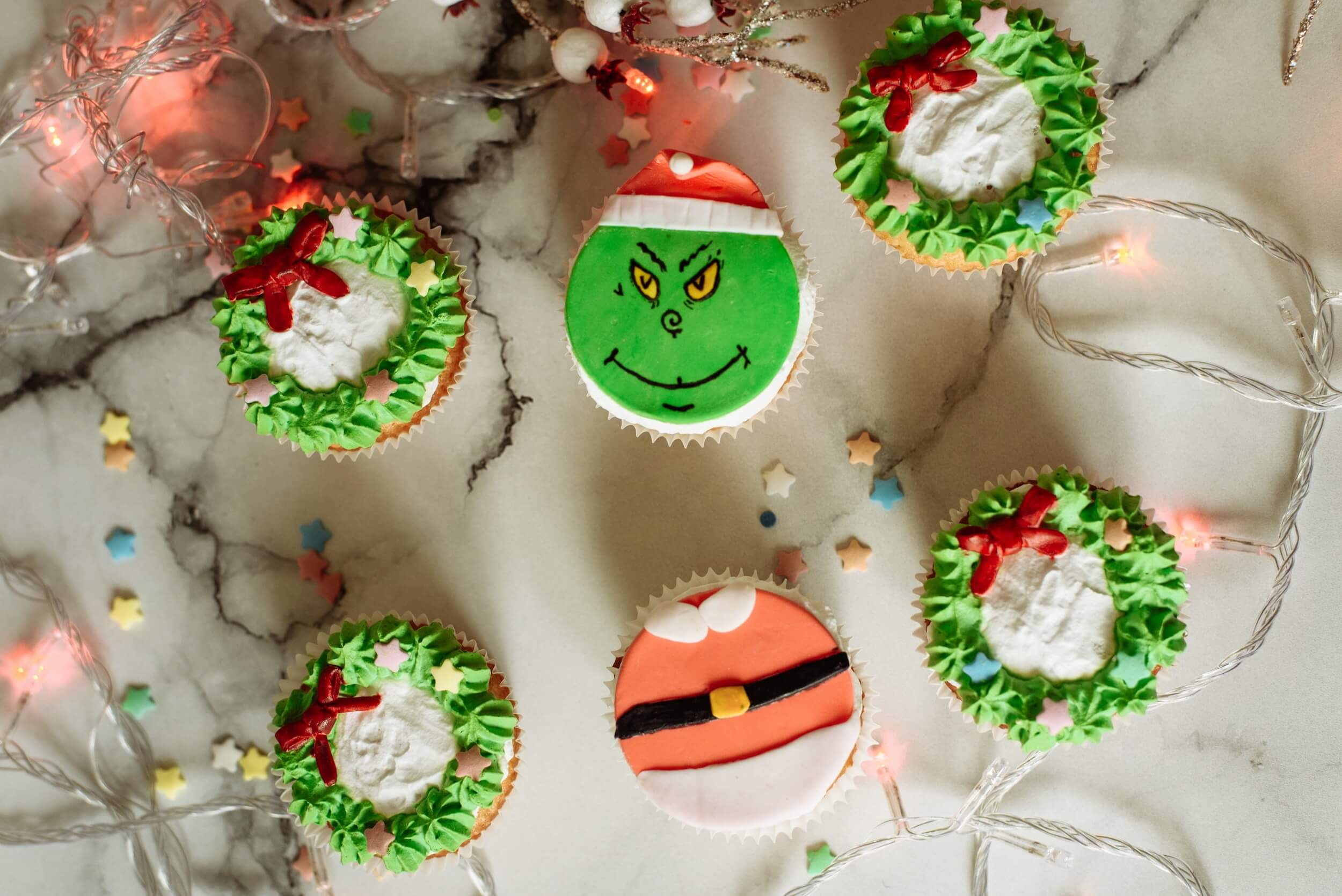 Christmas cakes in all colors, on of them is decorated as Grinch's face