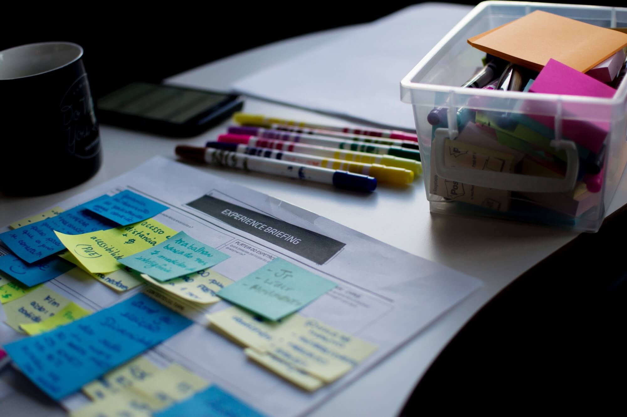 "sticky notes on a piece of paper titled ""Experience Brief"" surrounded by design tools — pens, phone, paper, coffee cup"