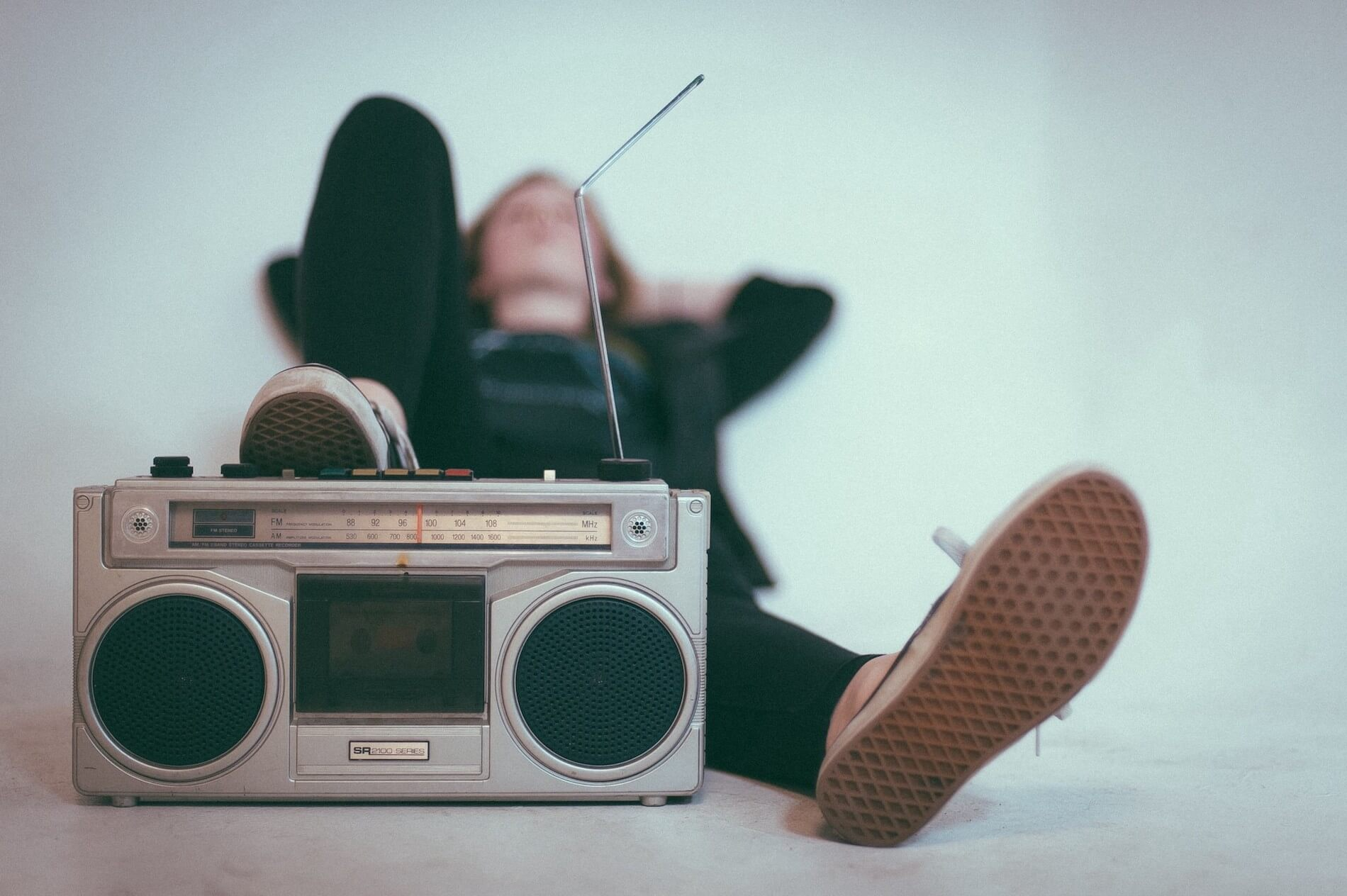 Out of focus person lying on their back with a sneaker on a boombox