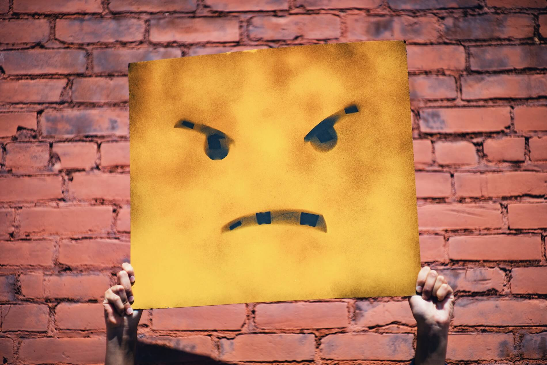 Angry face painted on rectangle yellow banner