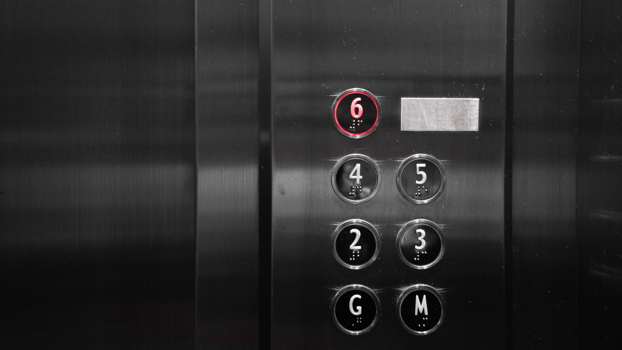 Bank of elevator buttons G, M, 2–6 with braille, 6th floor is lit up