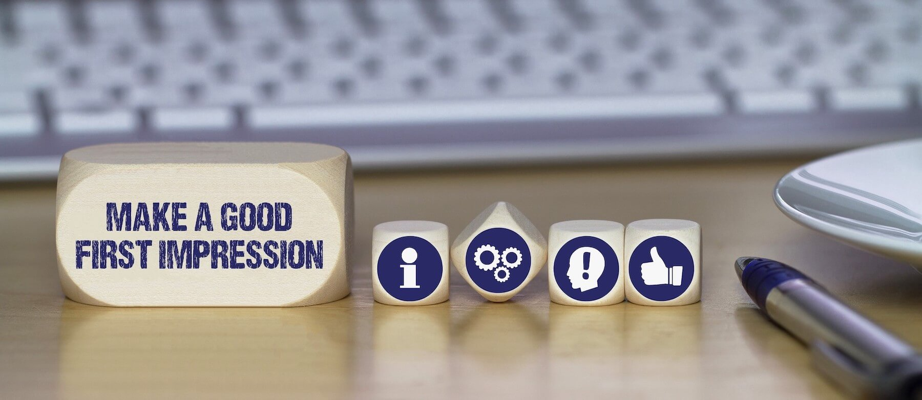 "Keyboard on desk behind social media icons on wooden cubes with the text ""make a good first impression"" on a larger rectangle"