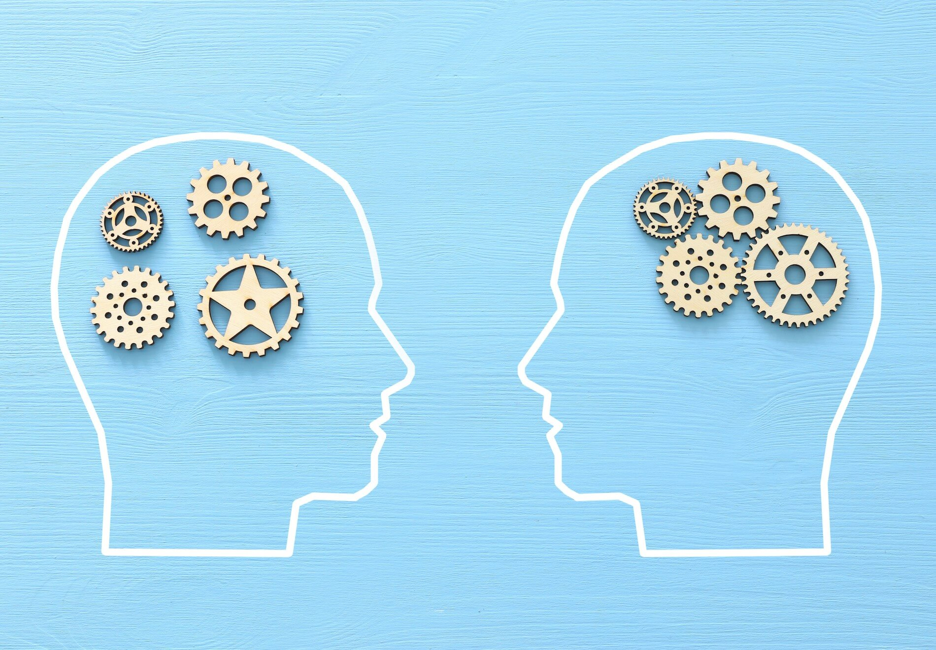 two cartoon heads with several gear wheels in the place of their brains looking at each other