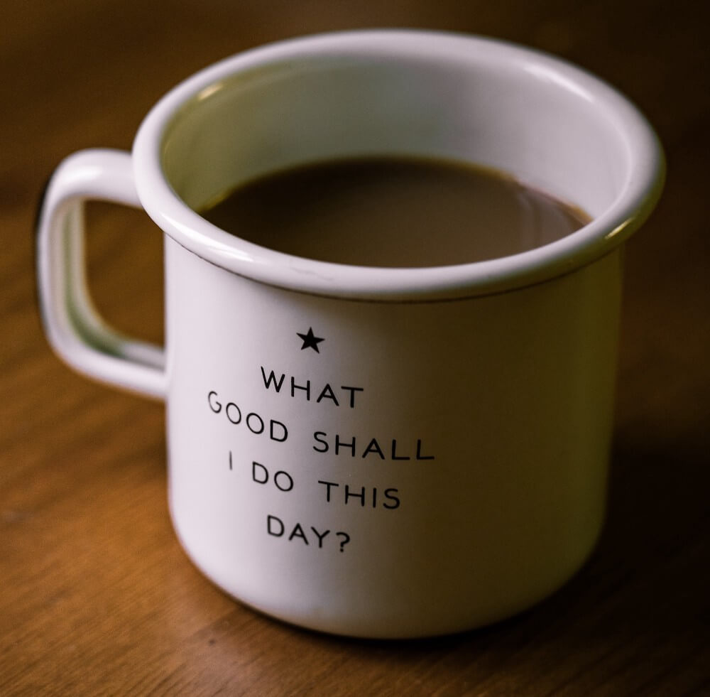 "Full white ceramic coffee cup that say ""What good shall I do this day?"""