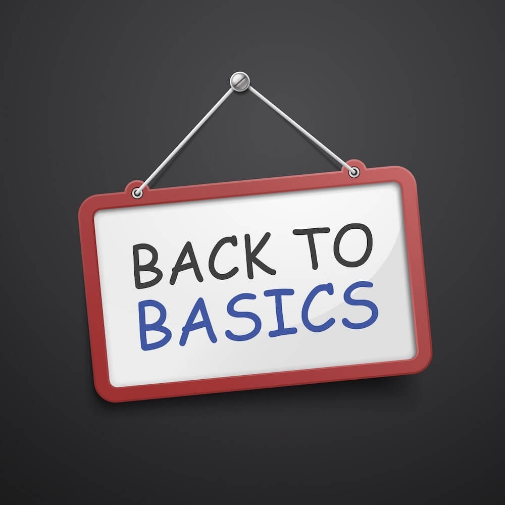 "Tilted sign that says ""Back to Basics"" hanging on black chalkboard"