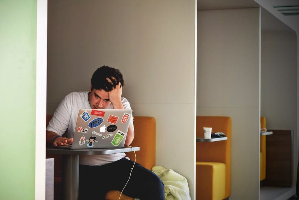 Man sitting in small working space with laptop looking frustrated