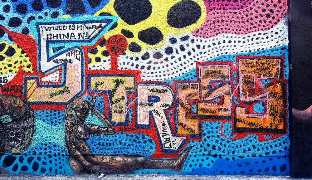 Graffiti-like art mural with bright colors spelling out the word Stress