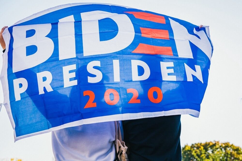 "Two people hidden behind ""Biden President 2020"" banner"