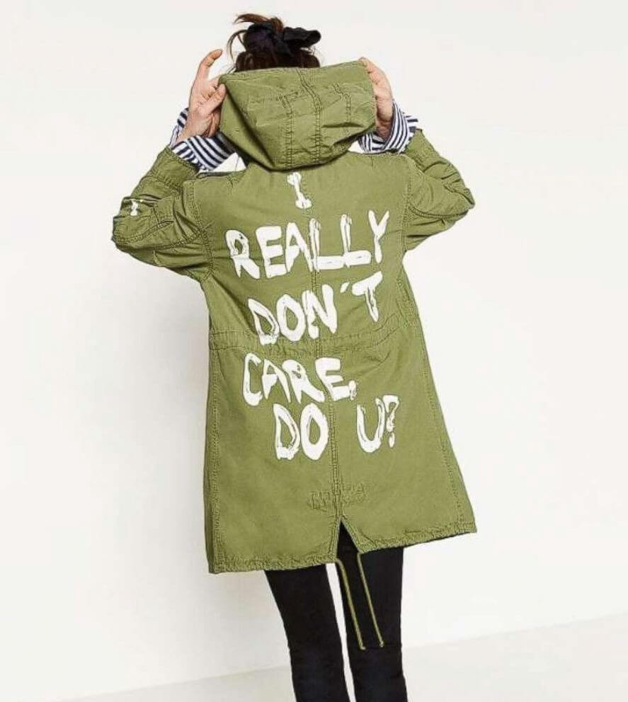 "Zara model wearing green jacket famously worn by Melania Trump. White block graffiti says ""I really don't care do u?"""
