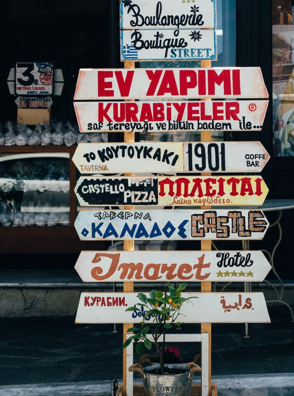 Street signs in several different foreign languages for a tavern, a pizza place, a castle and a hotel