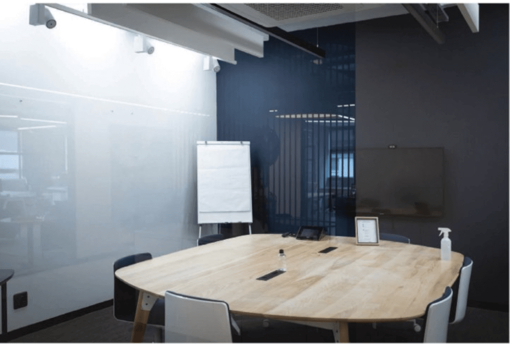 a conference room with a table an oval table, six chairs and white board next to it