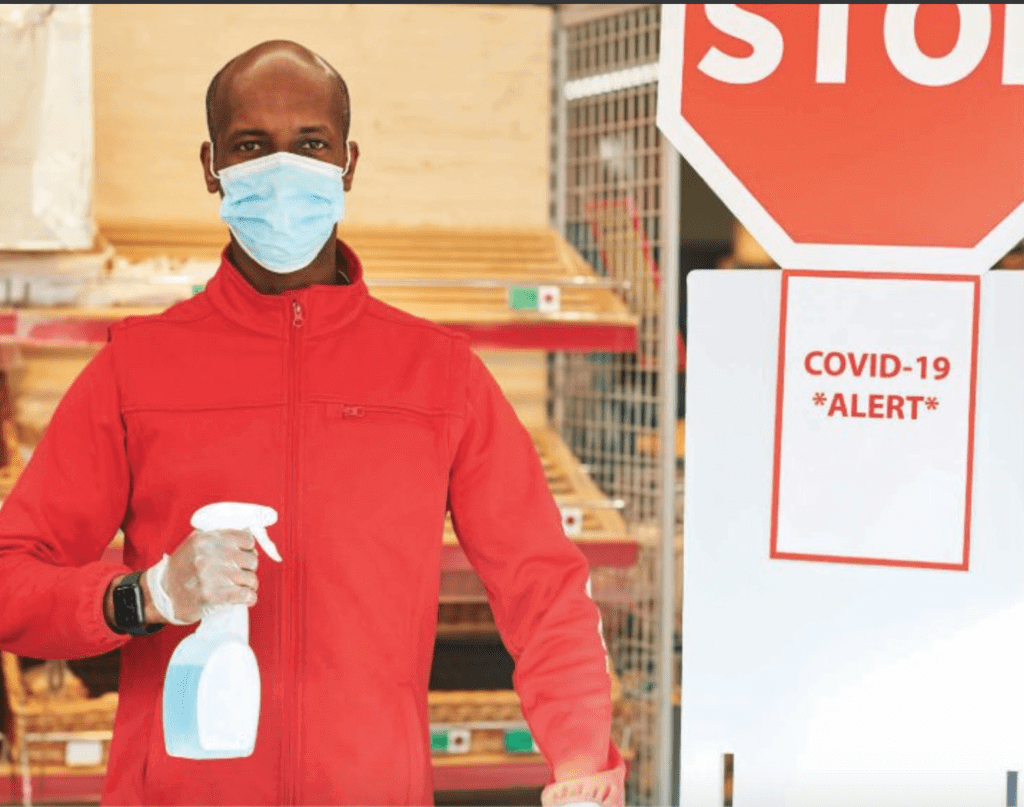 a black man wearing surgeon mask, hand sanitizer and standing next to covid alert 19 banner
