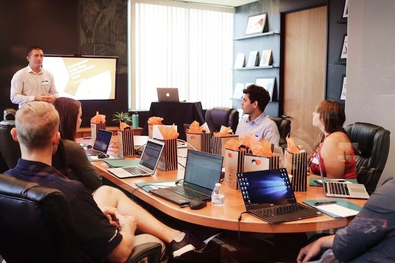 Person giving presentation in conference room with several diverse attendees with laptops