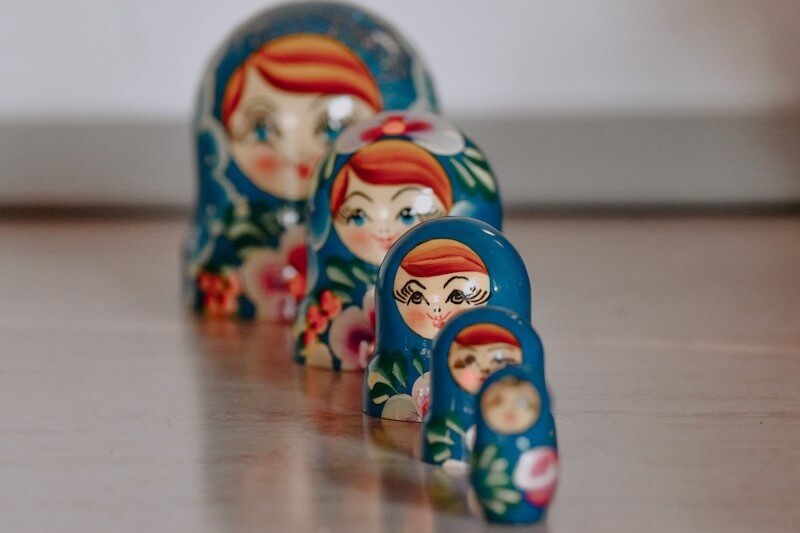 A series of five blue, wooden, Russian matryioshka dolls in a slightly angled vertical row, each smaller than the one behind it